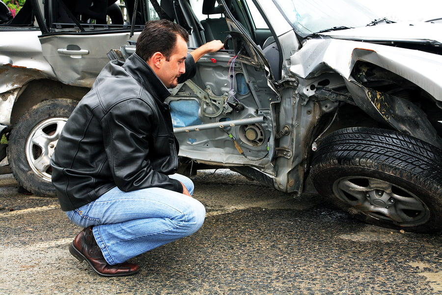 Man looking at the damage left from his auto accident
